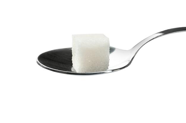 Kostka cukru w łyżce na białym tle
