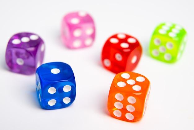 Kostka do gry w różnych kolorach odizolowywających na bielu.