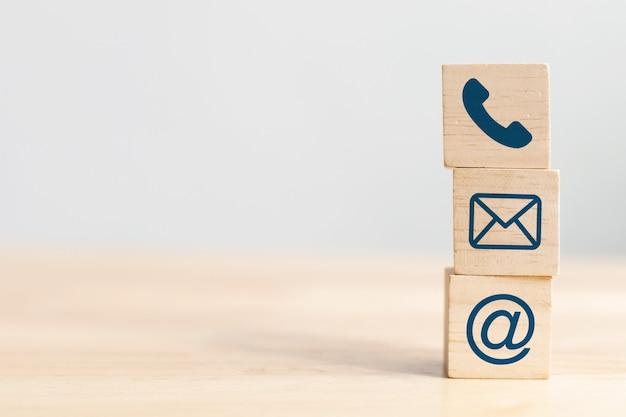 Kostka drewniana z telefonem, adresem e-mail i adresem. copyspace