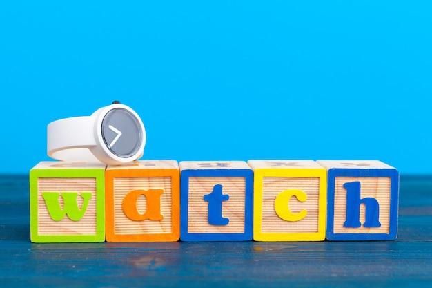 Kostka drewniany blok z alfabetu buduje zegarek słowo