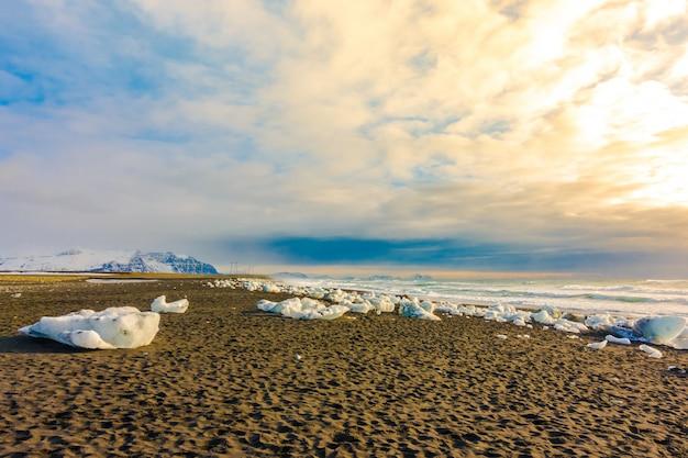 Kostka lodu łama na czerni skały plaży, iceland zimy sezonu krajobraz