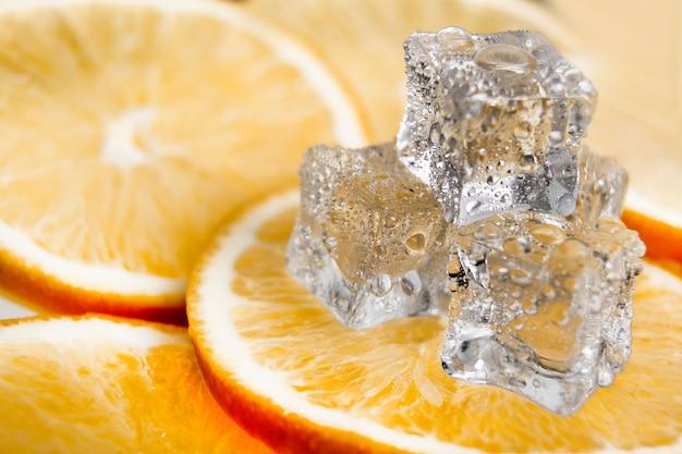 Kostka lodu na pomarańczowym tle. świeże pomarańcze