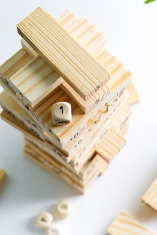 Kostka numer jeden na szczycie drewnianej piramidy z bloków na jasnoszarej ścianie. gra na zarabianie, rozwój i edukację.