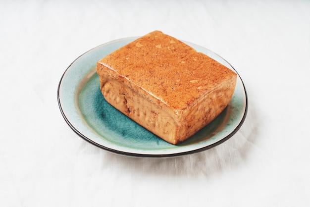 Kostka organicznego sera somoked tofu podawana na niebieskim talerzu na bambusowej macie. koncepcja wegańskiej przekąski