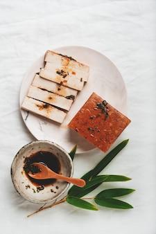 Kostka organicznego sera somoked tofu z sosem sojowym i liśćmi bambusa. leżał na płasko. widok z góry. koncepcja wegańskiej przekąski
