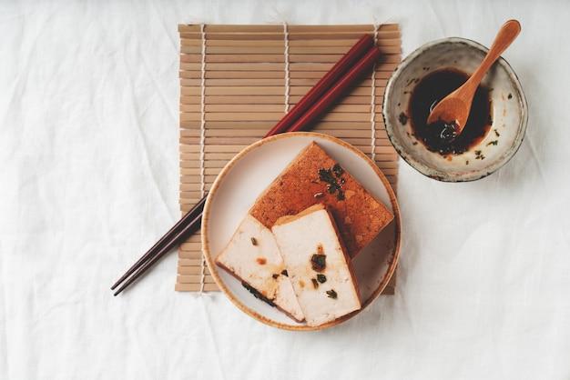 Kostka organicznego sera somoked tofu z sosem sojowym. leżał na płasko. widok z góry. koncepcja wegańskiej przekąski