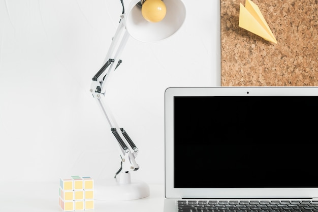 Kostka rubika, lampa stołowa w pobliżu otwartego laptopa