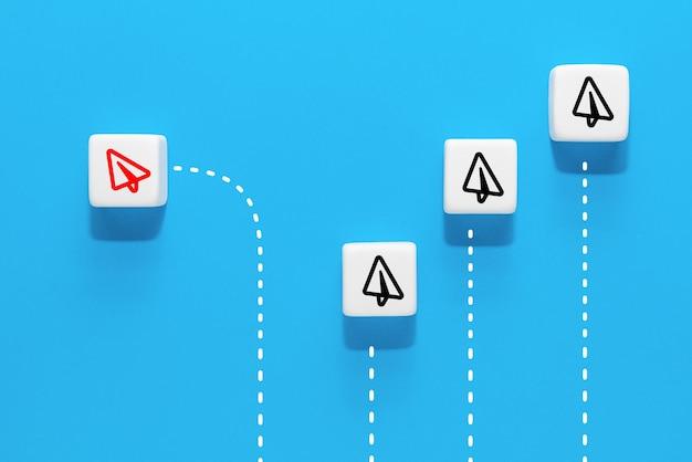 Kostka z wizerunkiem czerwonej papierowej ikony samolotu różniącej się od grupy, niebieskie tło, koncepcja biznesowa nowych pomysłów, kreatywność i innowacyjne rozwiązanie