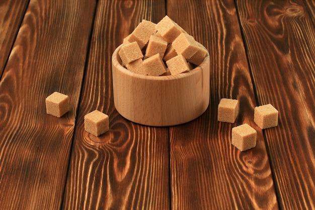 Kostki białego i brązowego cukru, drewniana miska na drewnianym stole. skopiuj miejsce