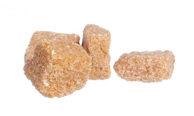 Kostki brązowego cukru na białym tle