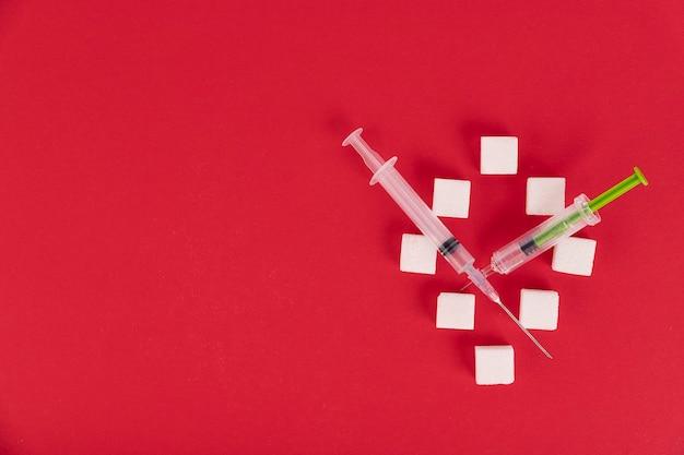 Kostki cukru białego i strzykawki na czerwonym tle w postaci cyfry zero. skopiuj spację.