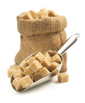Kostki cukru brązowego w czerpak na białym tle