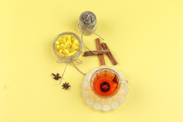 Kostki cukru, przyprawy, suszone zioła i herbata w szklanej filiżance