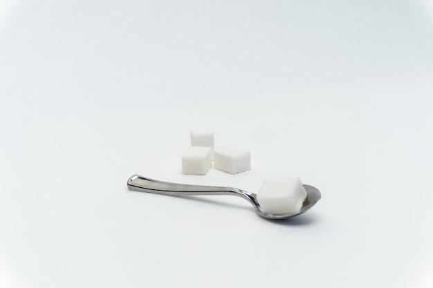 Kostki cukru w łyżeczce słodycze kaloryczność składnik glukoza. wysokiej jakości zdjęcie
