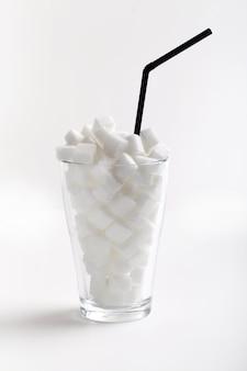 Kostki cukru w wysokiej szklance