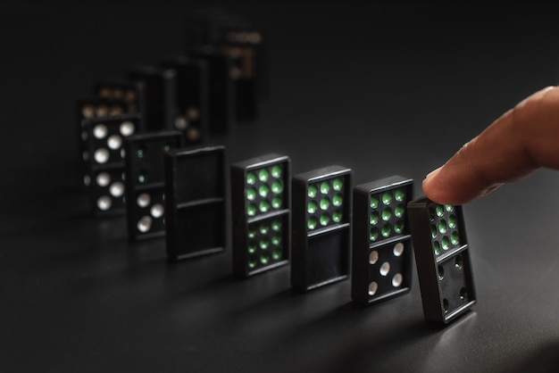 Kostki domina są umieszczone na czarnym tle. wszystkie domina spadają po naciśnięciu jednego palca. model biznesowy,