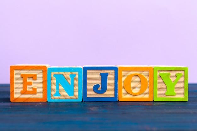 Kostki drewniany blok z alfabetu budowanie słowa cieszyć