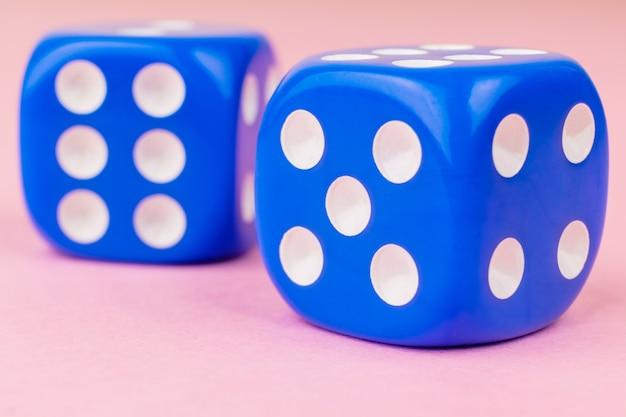 Kostki gry o niebieskim kolorze na jasnej pastelowej różowej powierzchni.