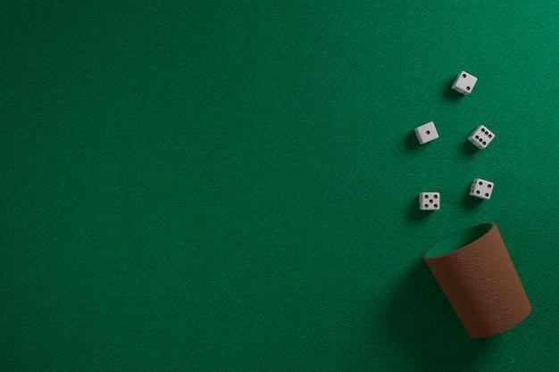 Kostki i kostki kubek na zielonej szmatce.