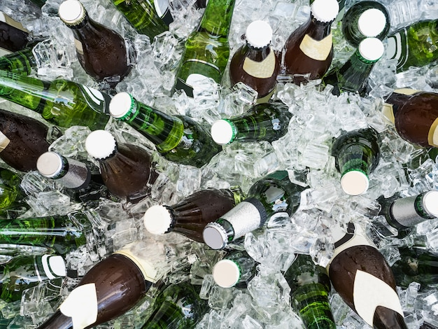 Kostki lodu i kolorowe butelki z zimnym piwem