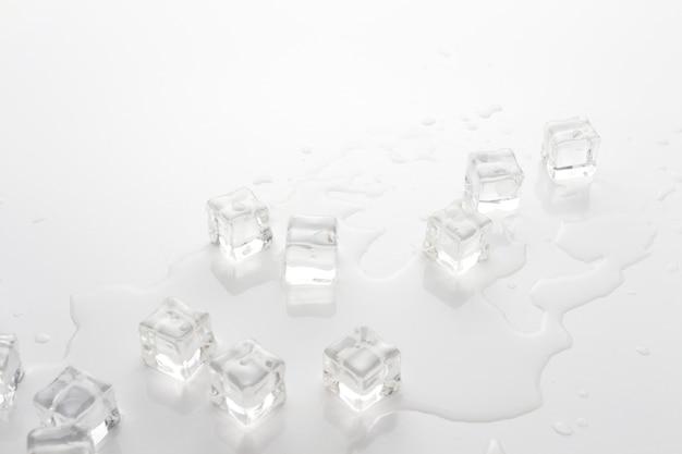 Kostki lodu i rozlana woda na jasnym tle