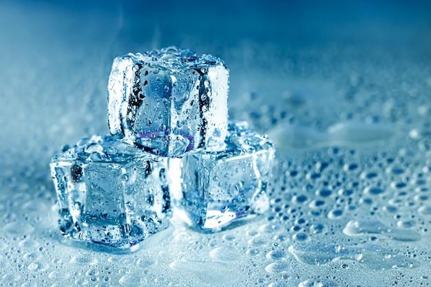 Kostki lodu i woda topią się na chłodnym tle. bloki lodu z zimnymi napojami lub napojami.