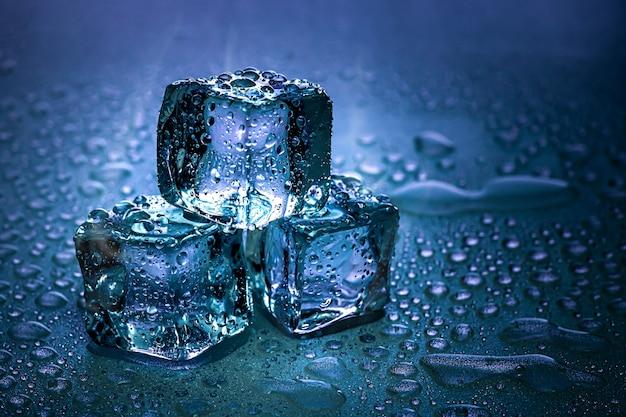 Kostki lodu i woda topią się na chłodnym tle