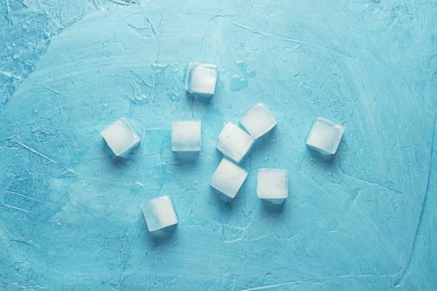 Kostki lodu na błękitnym kamiennym tle. kształt kwadratu. koncepcja produkcji lodu. leżał płasko, widok z góry