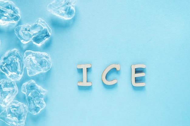 Kostki lodu na niebieskim tle. lodowe słowo napisane drewnianymi literami. widok z góry