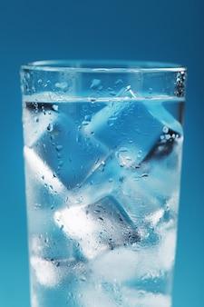 Kostki lodu w szklance z orzeźwiającą wodą lodową na niebieskim tle.
