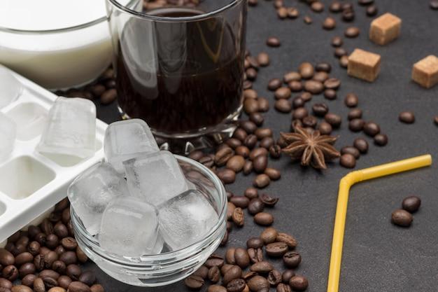 Kostki lodu w szklanej nakrętce. mleko w szklanej nakrętce. szkło z kawą. żółta słoma.