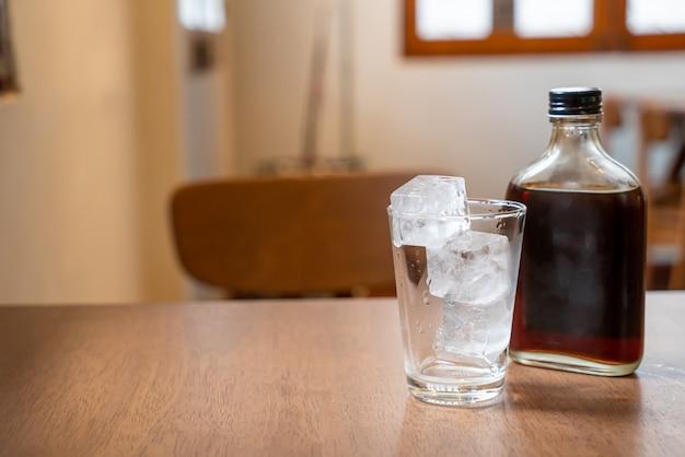 Kostki lodu w szkle z zimną kawą na drewnianym stole
