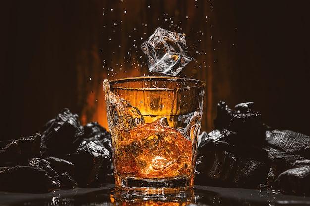 Kostki lodu wpadają do szklanki z brązowym napojem alkoholowym