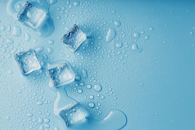 Kostki lodu z kroplami stopionej wody na niebieskim stole, widok z góry. świeżość w upale. napoje chłodzące