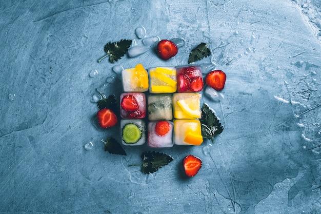 Kostki lodu z owocami i łamanym lodem na kamiennym niebieskim tle z liśćmi mięty i świeżymi owocami. kształt kostki. mięta, truskawka, wiśnia, cytryna, pomarańcza. leżał płasko, widok z góry