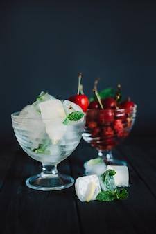 Kostki lodu z owocami i wiśniami na czarnym tle