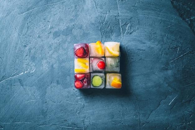 Kostki lodu z owocami na kamiennej niebieskiej powierzchni. kształt kwadratu. mięta, truskawka, wiśnia, cytryna, pomarańcza. leżał płasko, widok z góry