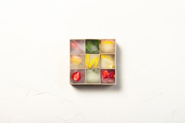 Kostki lodu z owocami w formie silikonowej na białej kamiennej powierzchni. koncepcja lodu owocowego, zaspokajanie pragnienia, lato. leżał płasko, widok z góry