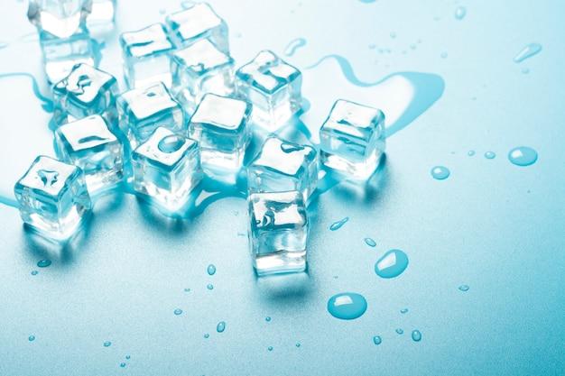 Kostki lodu z wodą na błękitnym tle. koncepcja lodu na napoje.