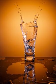 Kostki lodu zalewają szklankę wody, na pomarańczowej powierzchni z odbiciem
