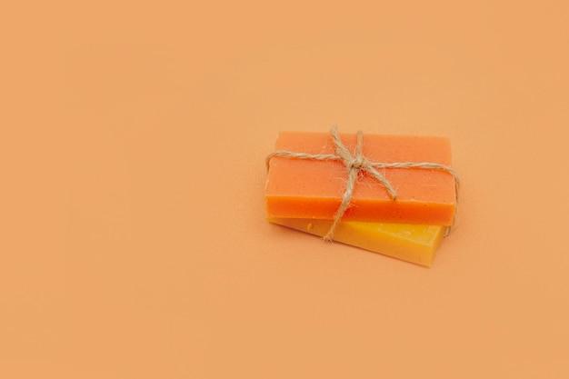 Kostki mydła brzoskwiniowo-morelowego, przewiązane sznurkiem na beżowym tle. ekologiczne naturalne kosmetyki ręcznie robione