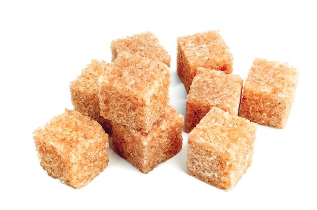 Kostki ryczałtowe brązowy cukier trzcinowy na białym tle na białej powierzchni.