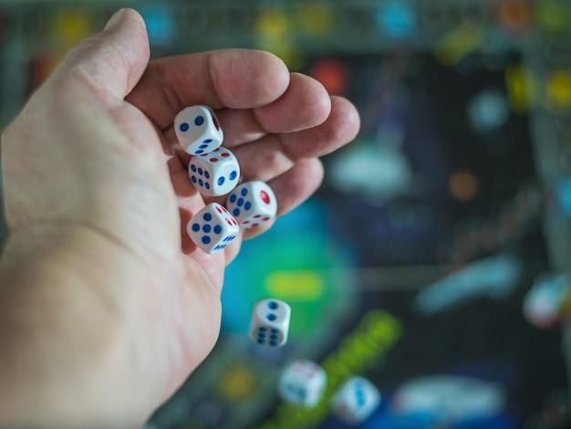 Kostki spadają z jego ręki na kolorową planszę.