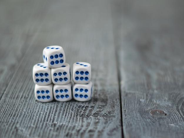 Kostki układane są w stos na drewnianym stole. numer sześć