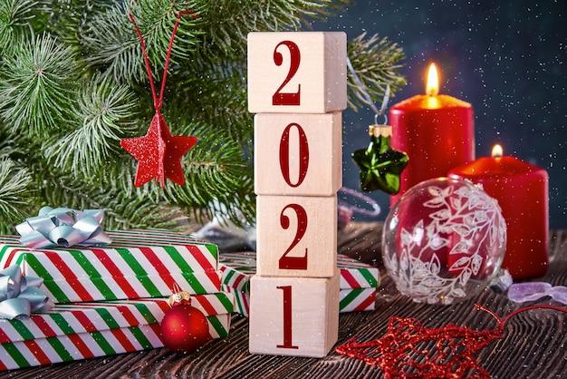 Kostki z numerami 2021 na świątecznym tle z prezentami w pudełkach, ozdobione gałązką świerkową i zapalonymi świecami. nowy rok w tle z wolnym miejscem na tekst.
