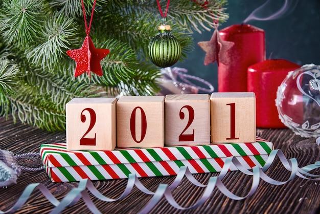 Kostki z numerami 2021 na świątecznym tle z prezentami w pudełkach, ozdobione gałązką świerkową i zgaszonymi świeczkami. nowy rok w tle z wolnym miejscem na tekst.
