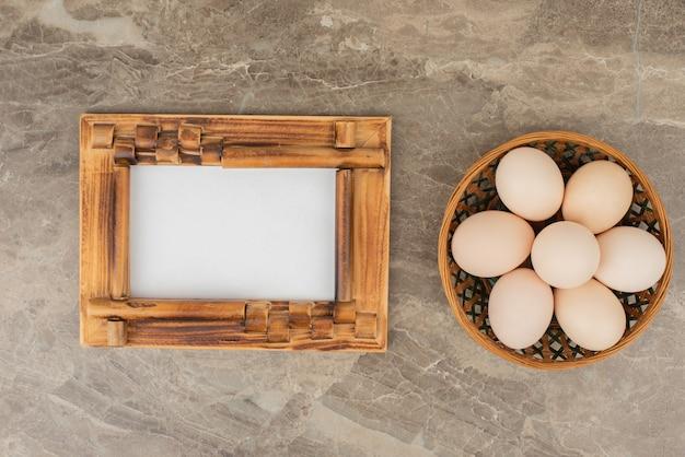 Kosz białych jaj na marmurowym stole.