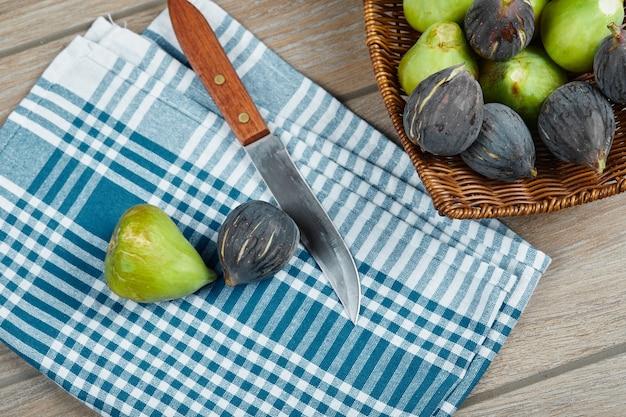 Kosz dojrzałych fig na drewnianym stole obok noża i obrusu.