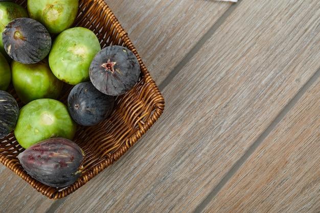 Kosz dojrzałych fig na drewnianym stole.