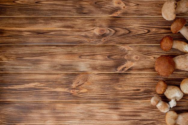 Kosz grzybów jadalnych: podgrzybek i borowik, rustykalne drewniane tło, selektywna ostrość, stonowany obraz.